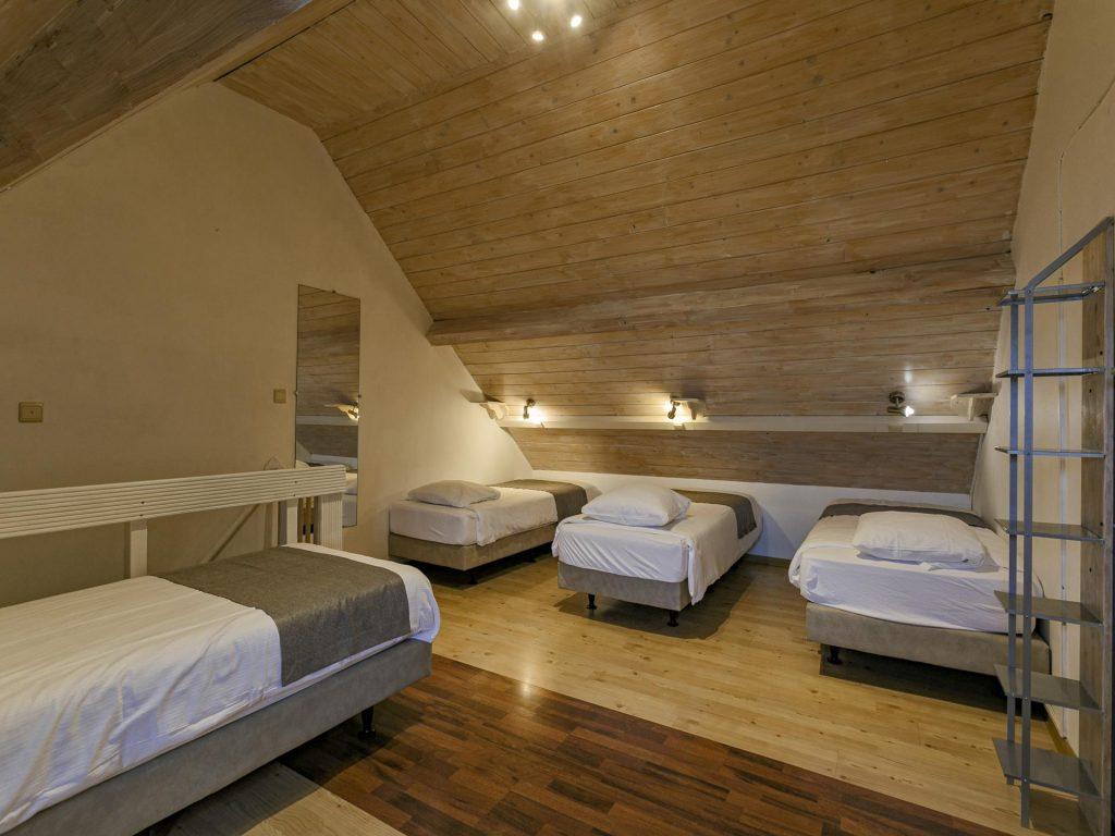 zespersoonskamer met vier single bedden boven